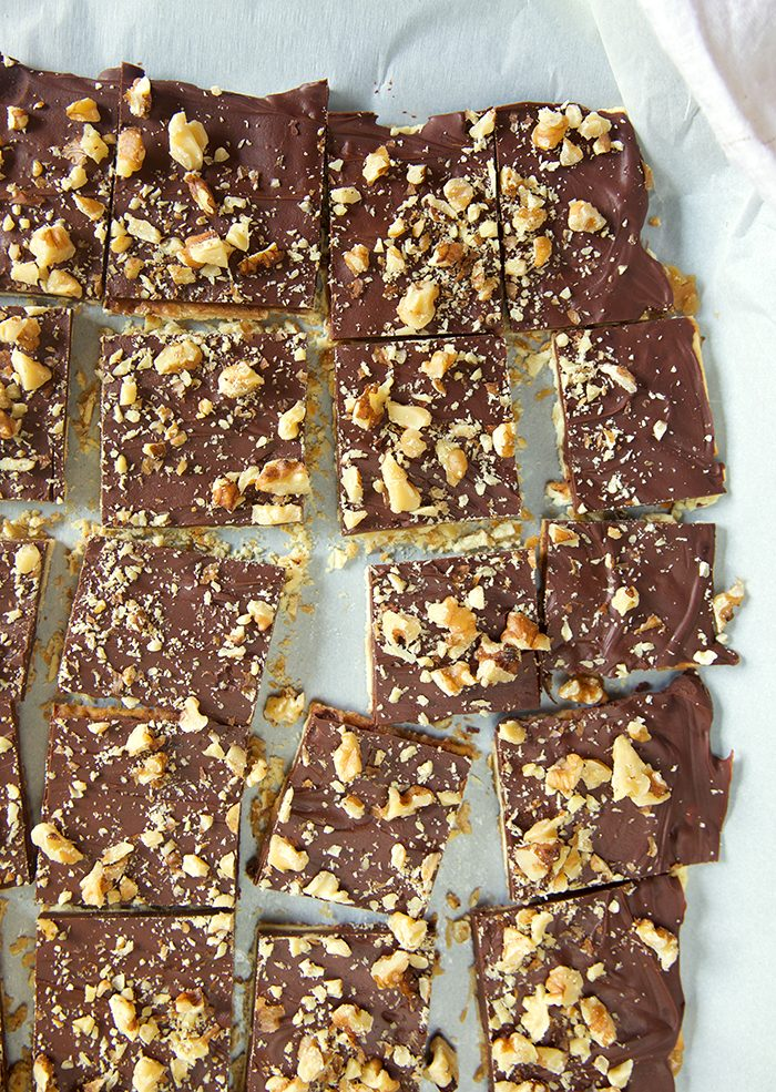 Overhead shot of Saltine Cracker Toffee cut into squares on a piece of white parchment.