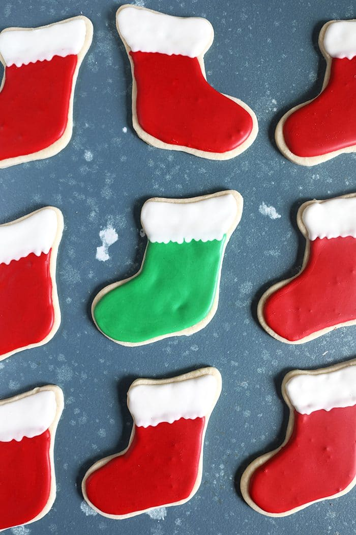 Red stocking cookies arranged in a line on a blue background.