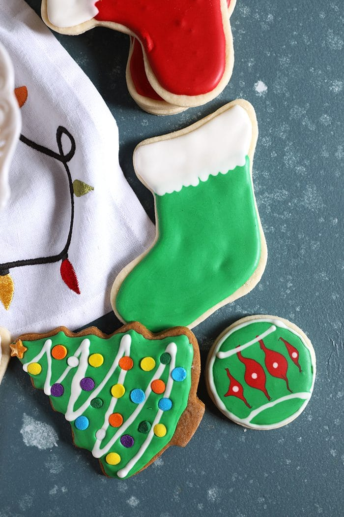 Overhead shot of a green stocking cookie and christmas tree cookie on a blue background.