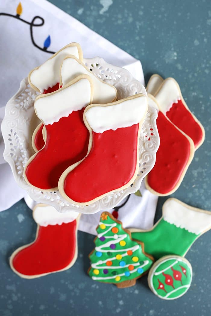 Stocking cut out cookies on a cake plate with a christmas tree cookie on a blue background.