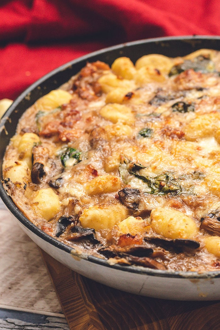 Baked Gnocchi in a skillet with a red napkin.