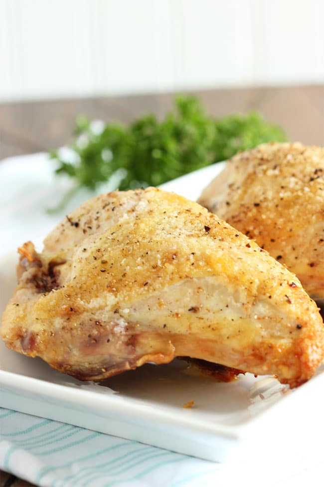 Oven Roasted chicken breast on a white platter with parsley in the background.