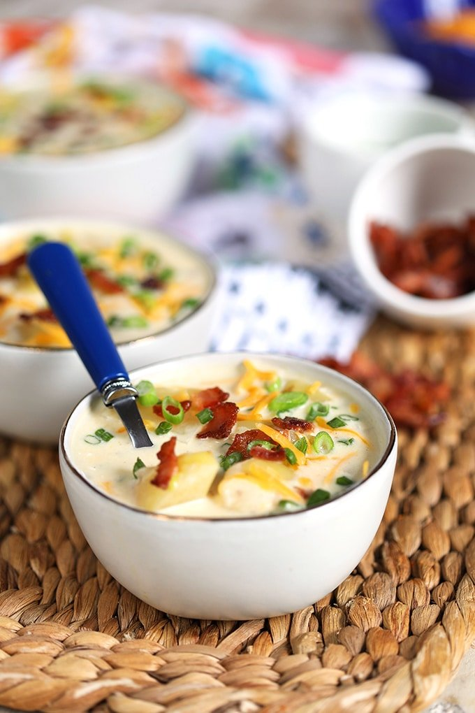 Loaded Baked Potato Soup in a white bowl with a blue spoon on a wicker placemat.