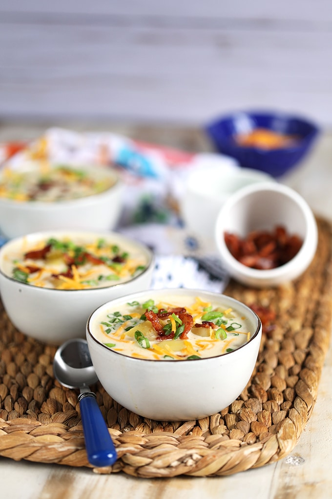 three white bowls of slow cooker loaded baked potato soup on a wicker mat.