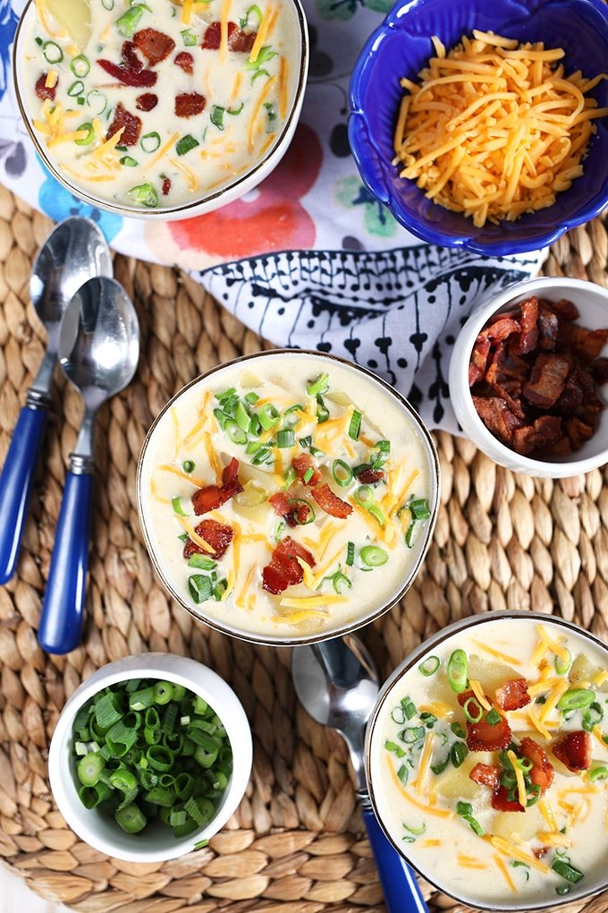 Overhead shot of three white bowls with slow cooker loaded baked potato soup and a bowl of chives and bacon.