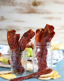 Sweet and spicy candied bacon in two mason jars.