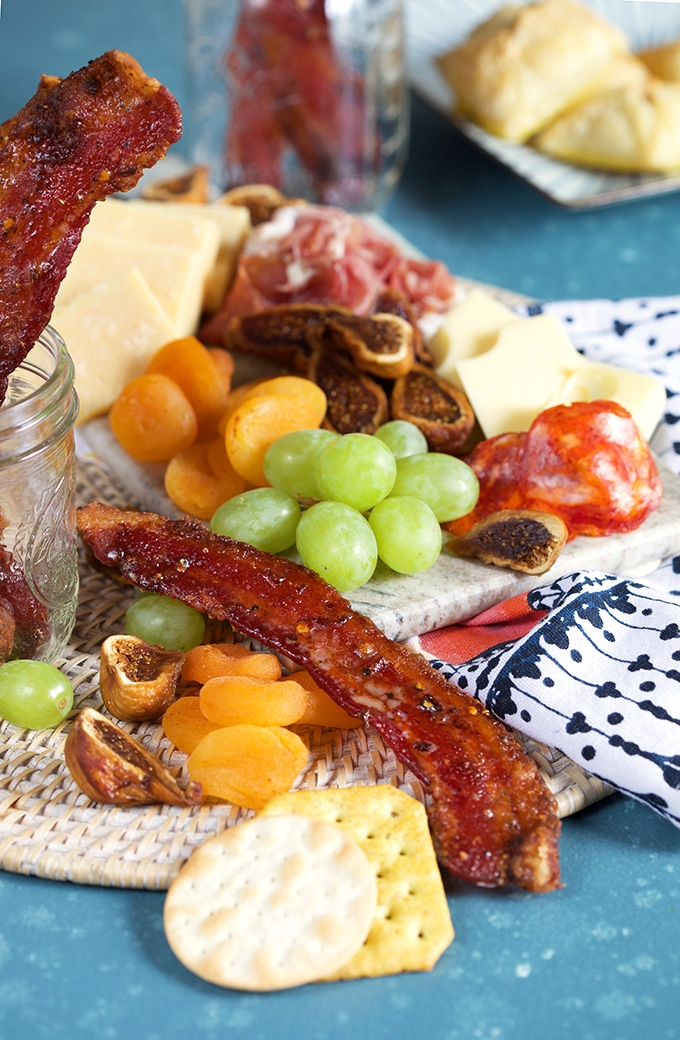 Sweet and spicy candied bacon on a charcuterie tray.
