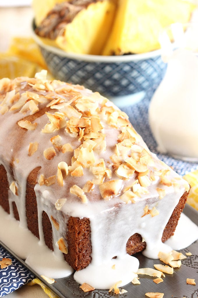 Pina Colada Banana Bread with Coconut Cream Glaze topped with toasted coconut flakes on a silver tray  | TheSuburbanSoapbox.com