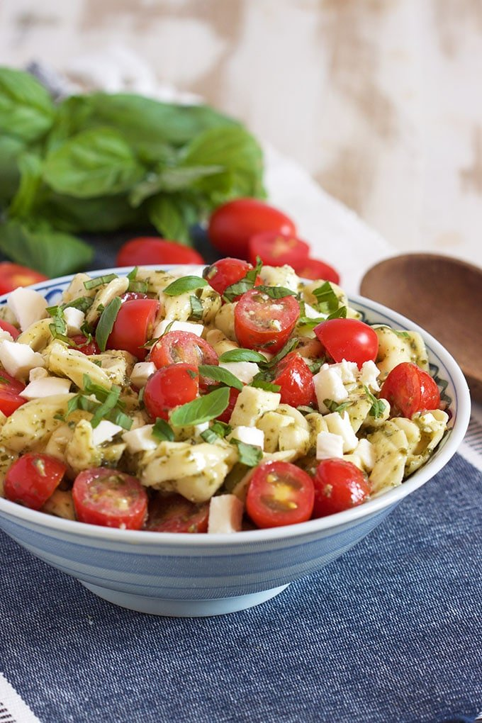 Bowl of Caprese Tortellini salad with basil and tomatoes in the background. | TheSuburbanSoapbox.com