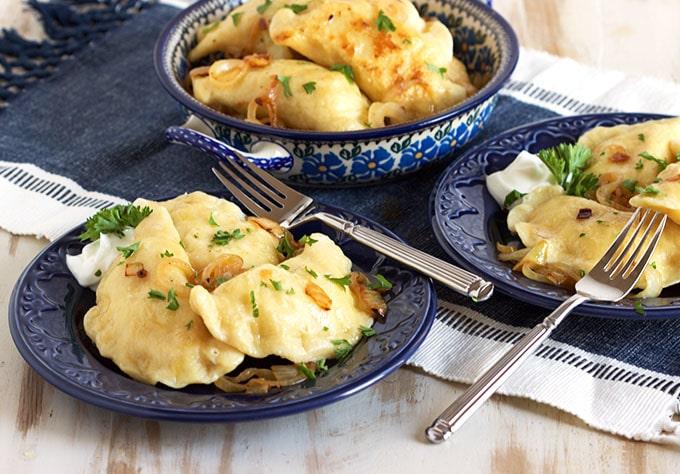 Potato pierogi on blue plates.