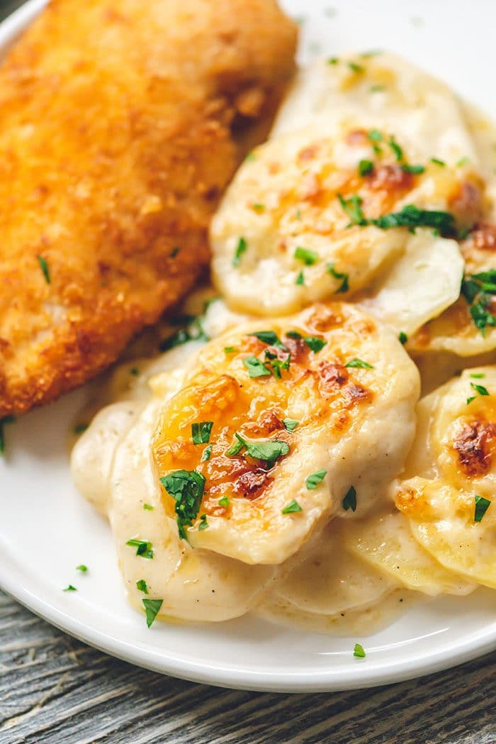 Au Gratin Potatoes on a white plate with crispy chicken.