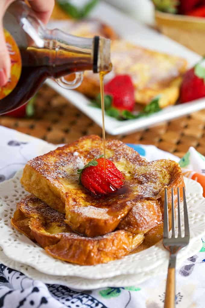Brioche French Toast with powdered sugar on a white place with maple syrup pour. | TheSuburbanSoapbox.com