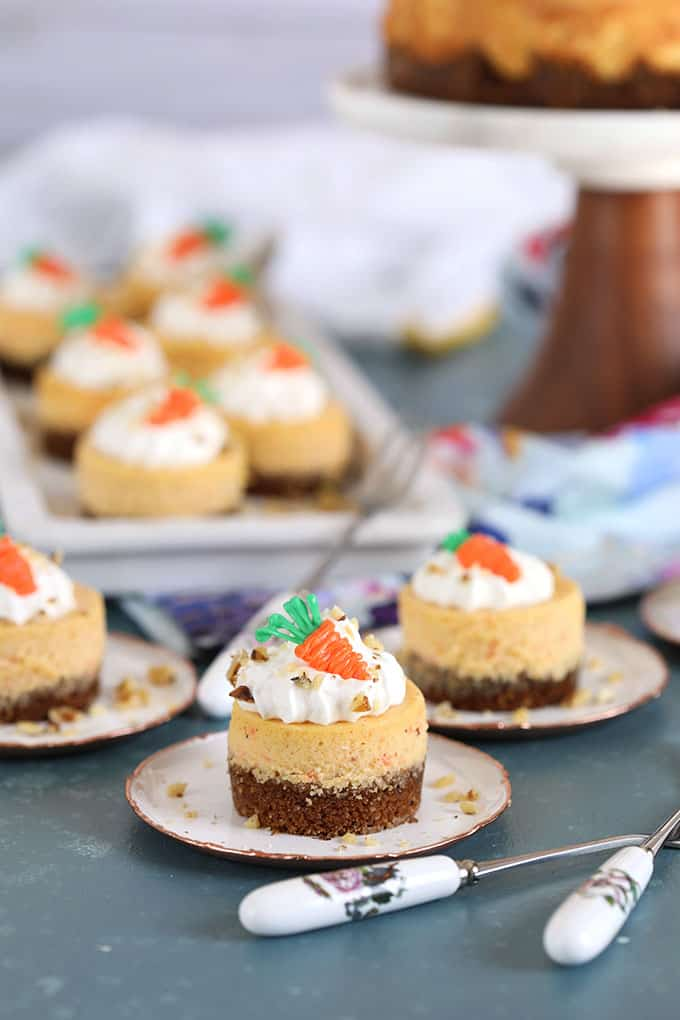 Mini Carrot Cheesecakes with chocolate carrots on white plates on a blue background from TheSuburbanSoapbox.com