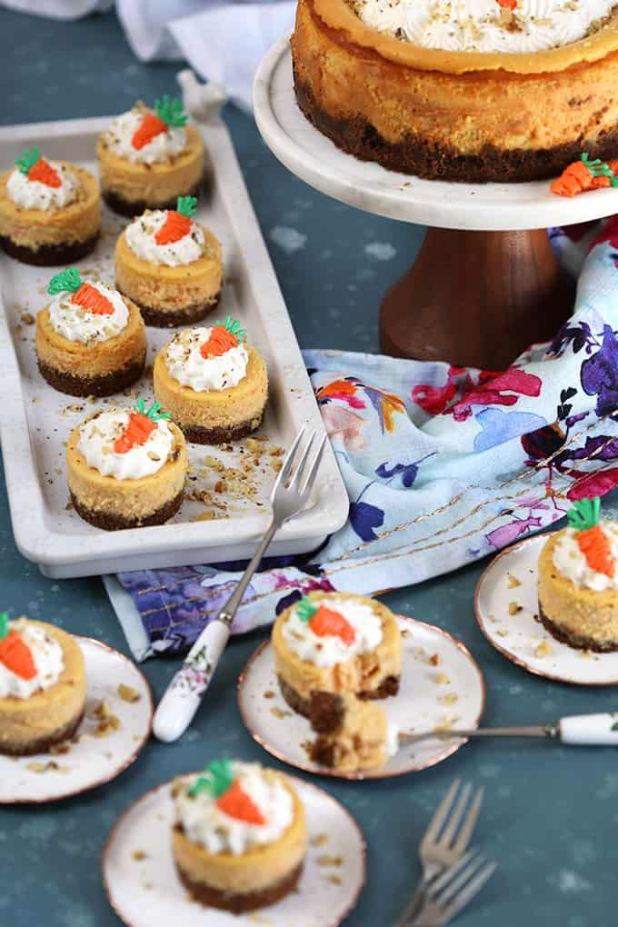 Assortment of different size Carrot Cheesecakes on white platters and a cake plate with a blue background from TheSuburbanSoapbox.com