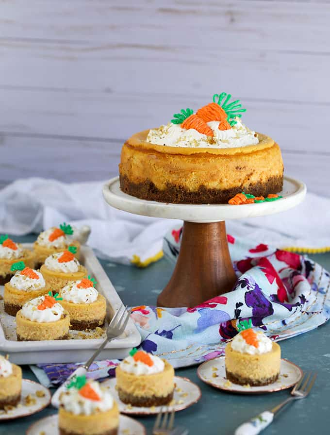 Assortment of Carrot Cheesecakes on a cake plate and mini plates on a blue background from TheSuburbanSoapbox.com