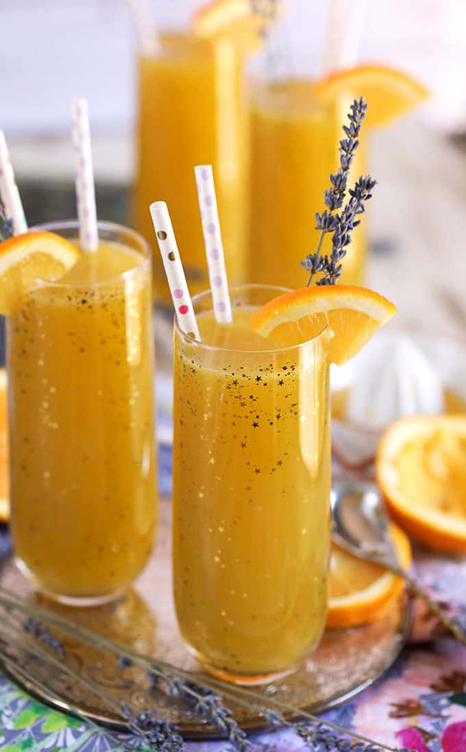 Lavender Orange Mimosa in a champagne flute with paper straws and lavender sprigs from The Suburban Soapbox .com