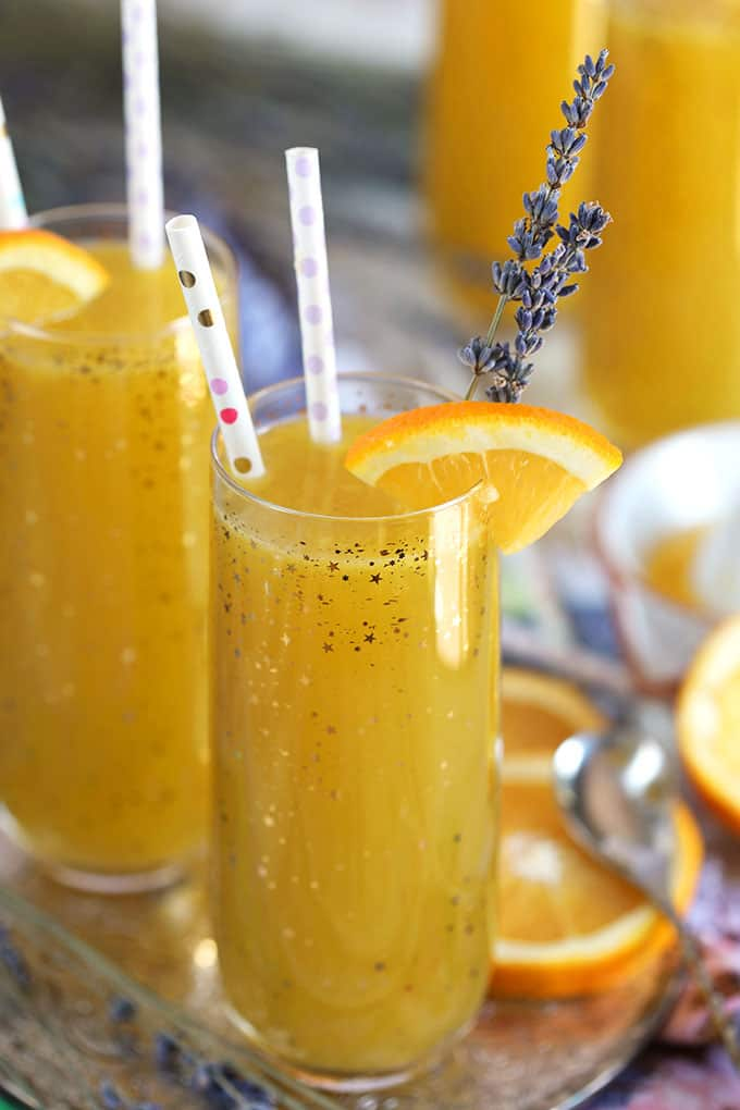 Lavender Orange Mimosa with paper straws in a champagne glass from TheSuburbanSoapbox.com