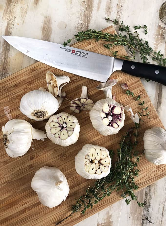 Garlic Bulbs with tops cut off on cutting board with chef's knife from TheSuburbanSoapbox.com
