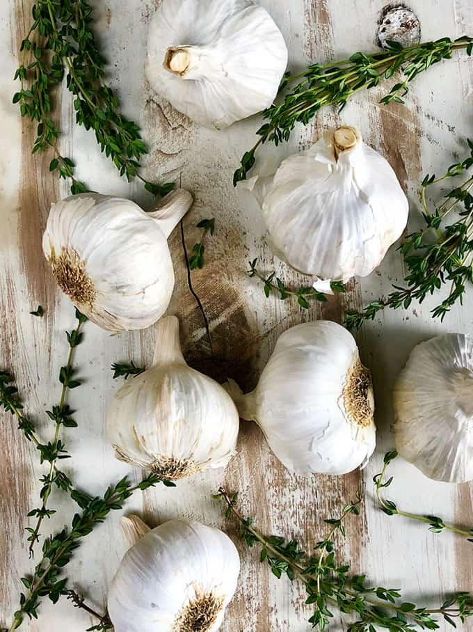 Garlic bulbs and thyme on a whitewashed cutting board. TheSuburbanSoapbox.com
