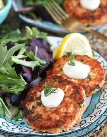 Two salmon cakes with lemon dill sauce on a decorative blue and white plate with a gold fork from TheSuburbanSoapbox.com