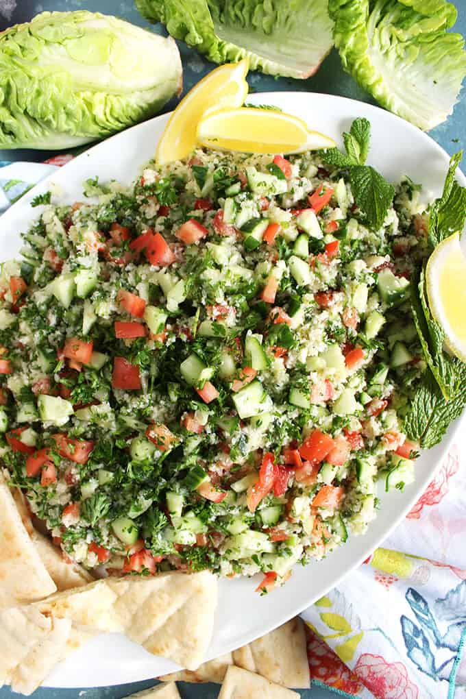 Cauliflower Rice Tabbouleh Salad on a white platter with pita bread and lemons from TheSuburbanSoapbox.com