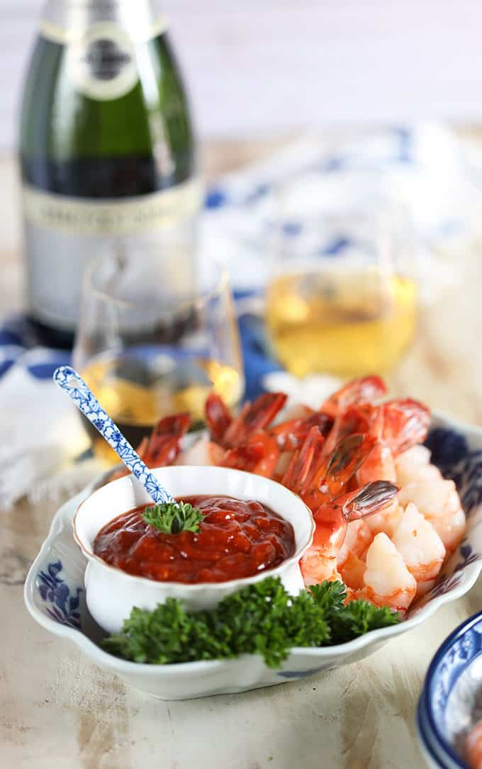 Homemade Cocktail sauce with shrimp on a blue and white plate with wine on a white background from TheSuburbanSoapbox.com