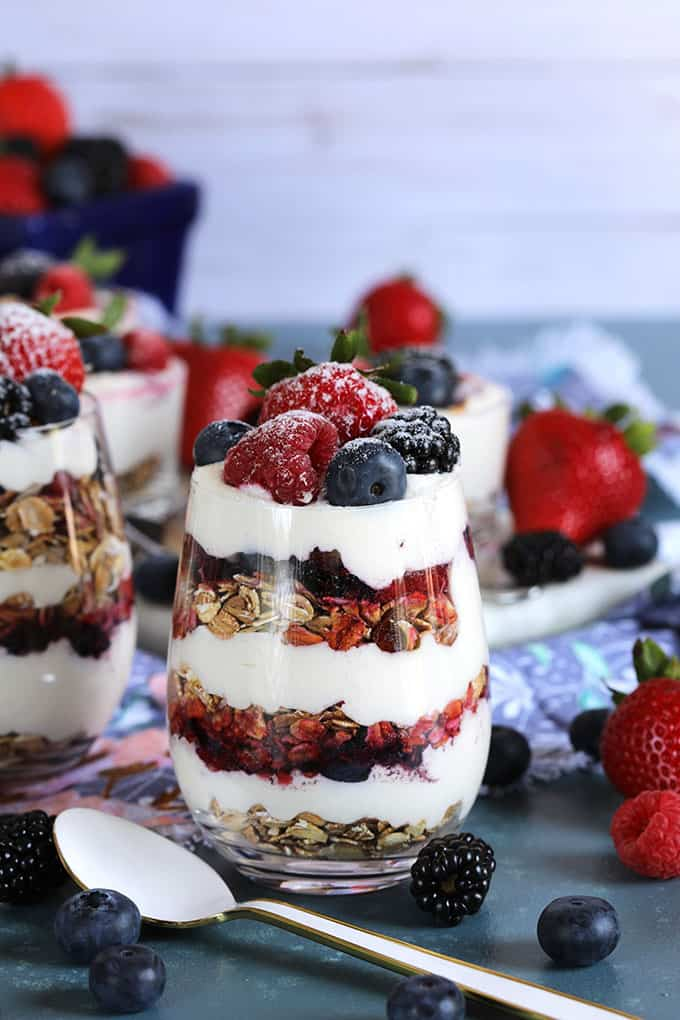 Layered cheesecake parfait with berries and muesli in a wine glass on a blue background from TheSuburbanSoapbox.com