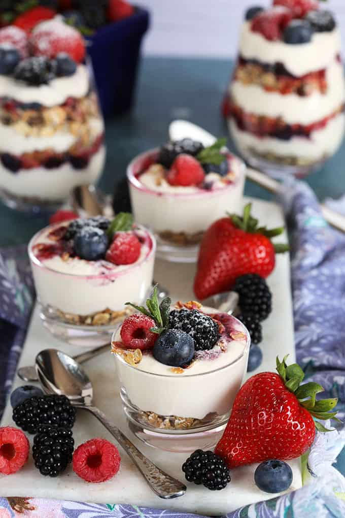 No Bake Cheesecake Breakfast Parfaits in a glass jar on a blue background with berries and a white spoon from TheSuburbanSoapbox.com
