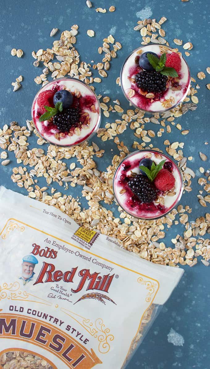 Three mini Breakfast Parfaits in a pile of muesli with a Bob's Red Mill Muesli bag on a blue background from TheSuburbanSoapbox.com
