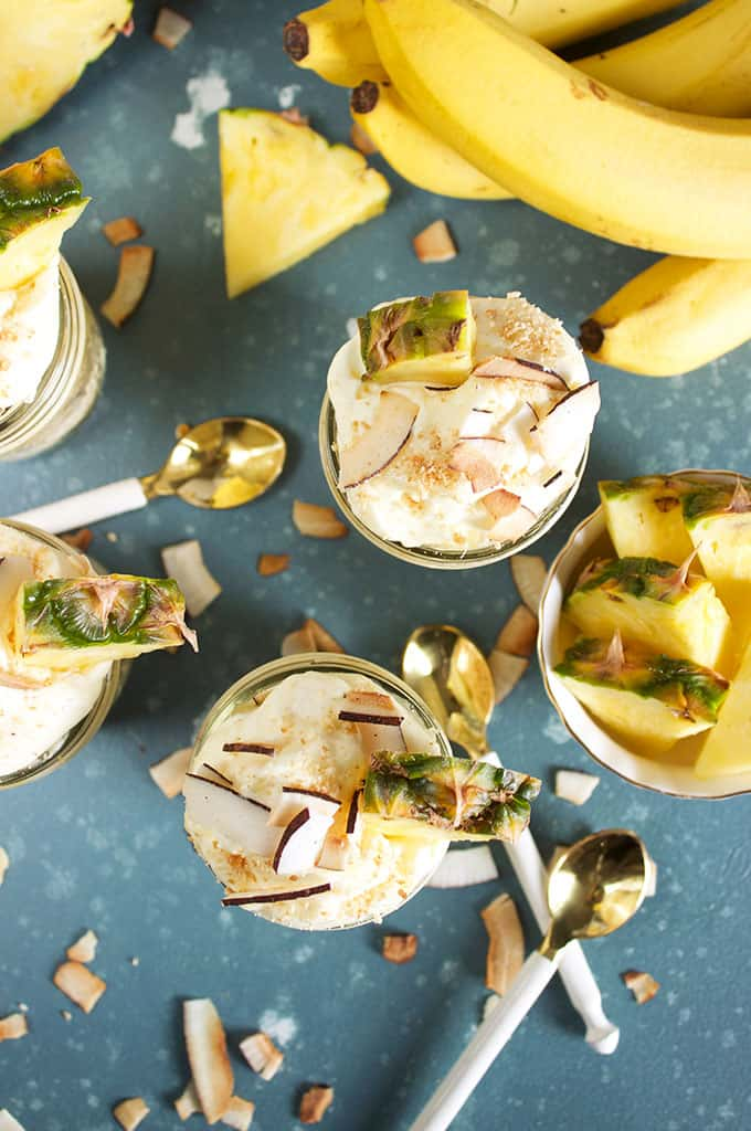 Overhead shot of three Pina Colada Banana Pudding recipe with bananas and pineapples on a blue background from TheSuburbansoapbox.com