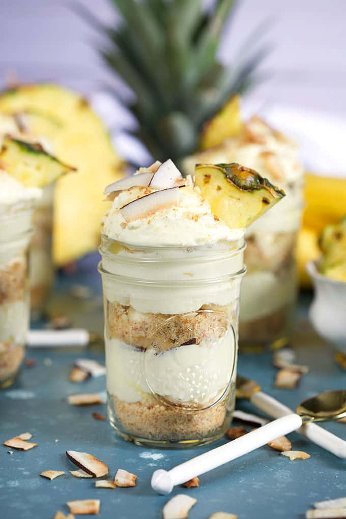 Layered Pina colada Banana Pudding in jars with pineapple on a blue background from ThesuburbanSoapbox.com