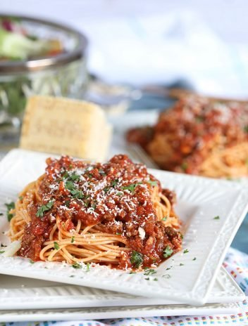 Spaghetti with Easy Italian Meat Sauce on a white plate with a blue background from TheSuburbanSoapbox.com