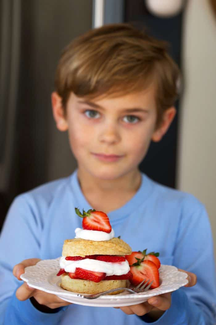 Landon holding on of the very Best Strawberry Shortcake recipe on a blue plate from Thesuburbansoapbox.com