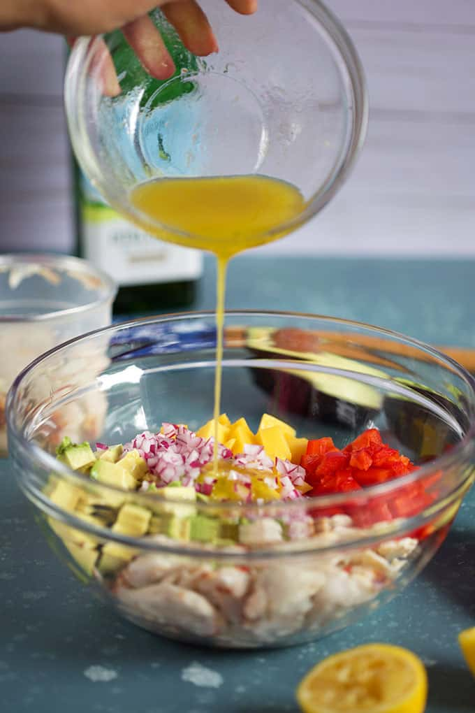 Dressing being poured on Mango Crab Avocado Salad in a glass bowl from TheSuburbanSoapbox.com