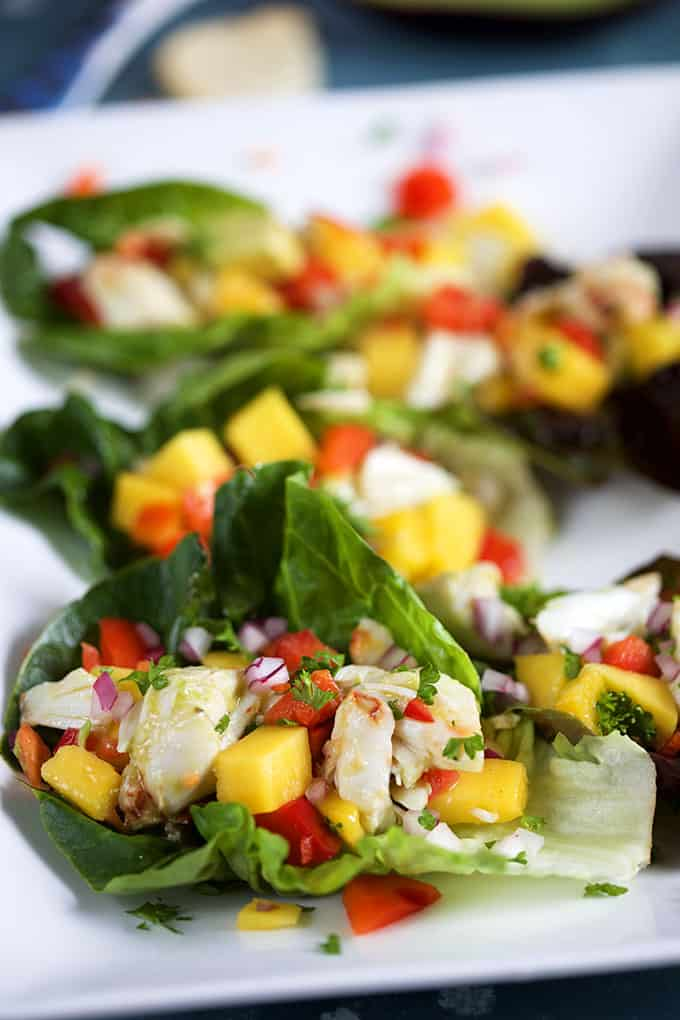 Mango Crab Avocado Salad on lettuce leaves on a blue platter from TheSuburbanSoapbox.com