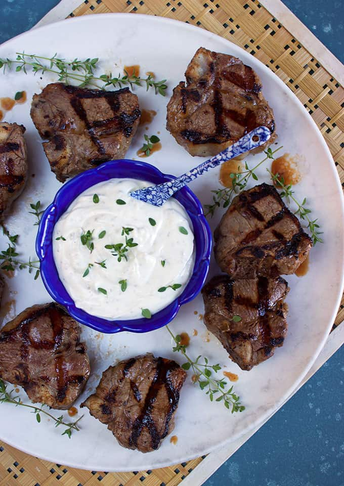 Grilled lamb chops on a round white platter with a blue bowl filled with goat cheese sauce from thesuburbansoapbox.com
