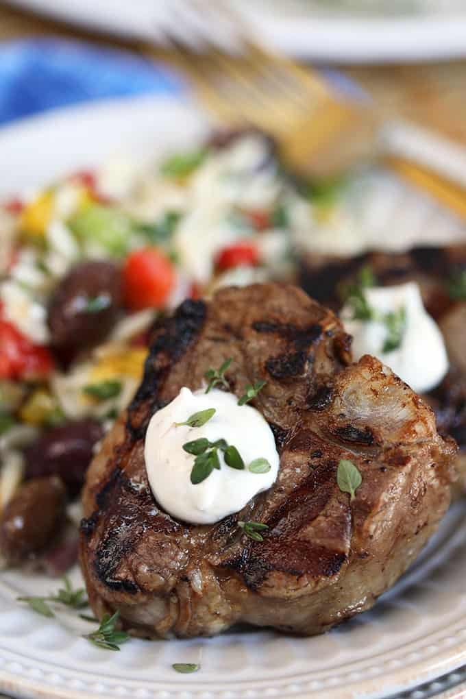 Close up shot of grilled balsamic lamb chops with goat cheese sauce on a white plate from TheSuburbansoapbox.com