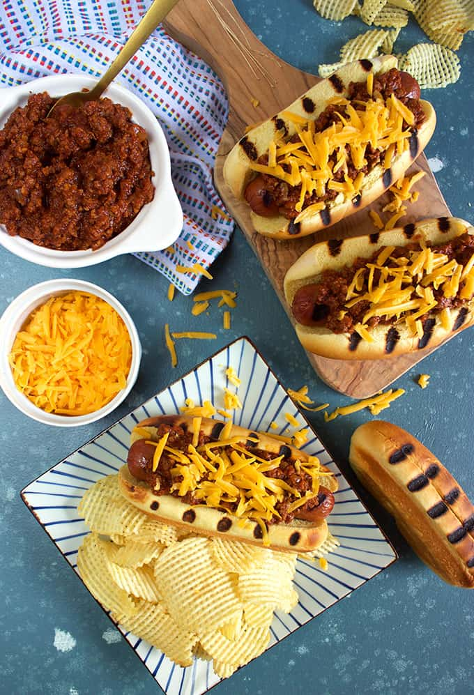 Overhead shot of three chili cheese dogs with potato chips on a blue background from TheSuburbansoapbox.com