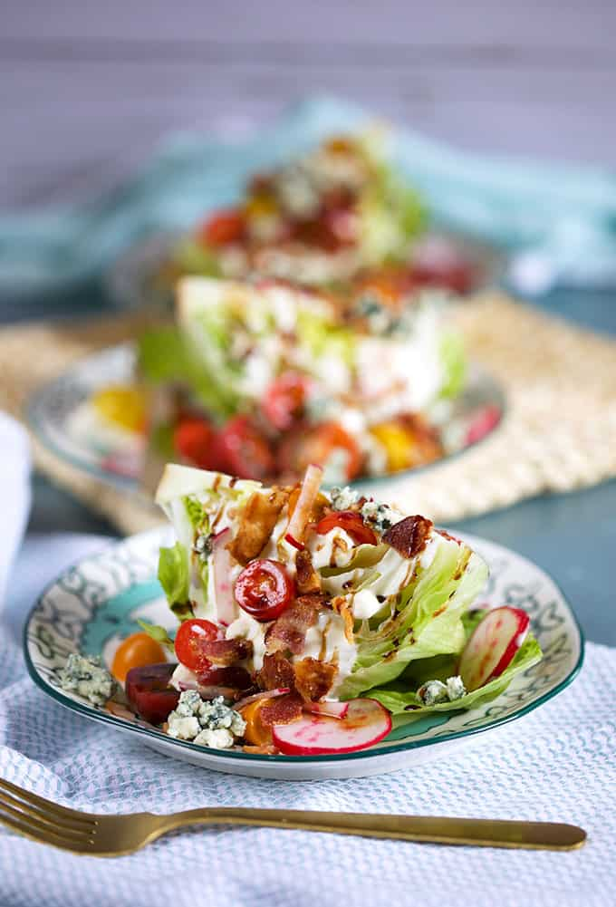Row of three Loaded Iceberg Wedge Salads on white and blue plates with a gold fork on a blue background from TheSuburbansoapbox.com