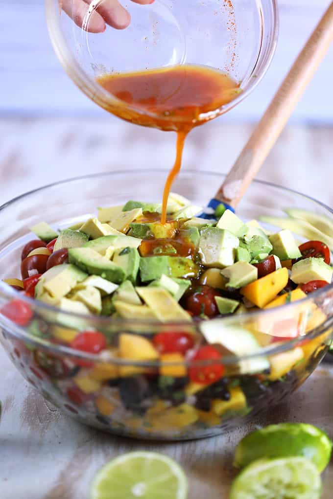 Ingredients for Mango Guacamole Salad in a glass bowl with dressing being poured over top.