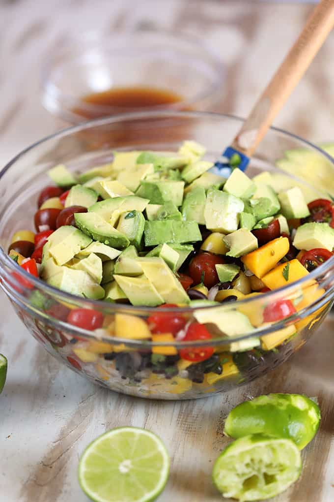 Ingredients for Chili Spiced Mango Guacamole Salad in a glass bowl.