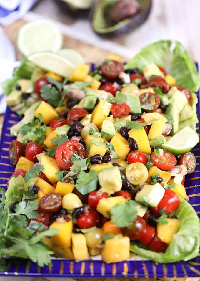 Mango Guacamole Salad on a blue and gold platter with lettuce, limes and avocado around it. From TheSuburbanSoapbox.com
