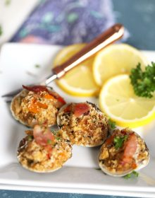 Clams Casino on a white plate with a copper fork from Thesuburbansoapbox.com
