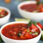 Tomato Gazpacho in a white bowl on a blue background from TheSuburbanSoapbox.com