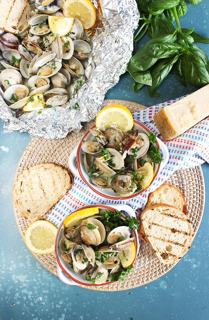 Overhead shot of grilled clams with parmesan, basil and grilled bread on a blue background.