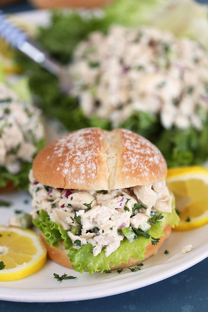 Lemon Tarragon Chicken Salad on a white roll with lettuce and lemon slices from TheSuburbanSoapbox.com