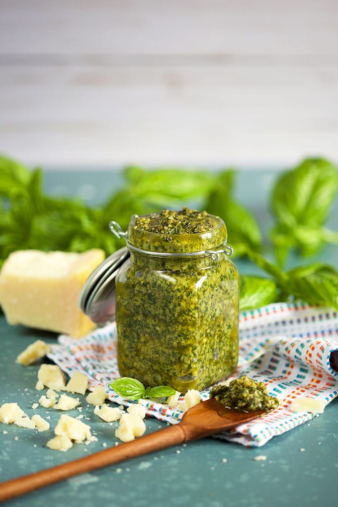 The Very Best Basil Pesto Sauce in a glass jar with a wooden spoon on a blue background with basil leaves in the background from TheSuburbanSoapbox.com