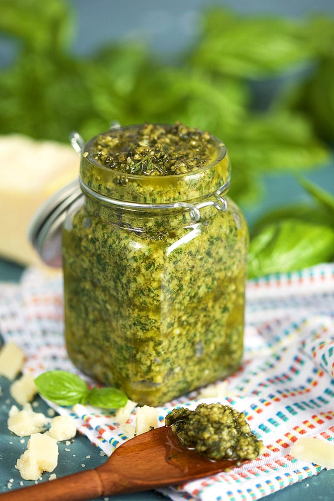 Basil Pesto in a glass jar with a wooden spoonful of basil pesto on a white striped napkin and basil leaves in the background from TheSuburbanSoapbox.com