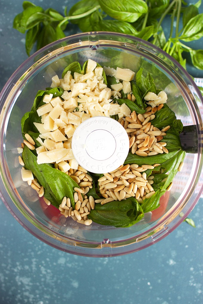 Ingredients for the Very Best Pesto recipe in the bowl of a KitchenAid Food Processor from TheSuburbanSoapbox.com