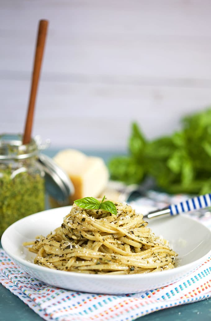 Pasta with Basil Pesto Sauce in a white bowl with a jar of basil pesto in the background from TheSuburbanSoapbox.com